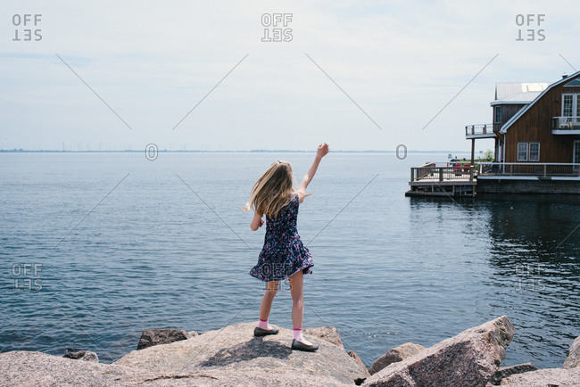 Blond haired girl waving from lakeside, rear view, Kingston, Ontario, Canada