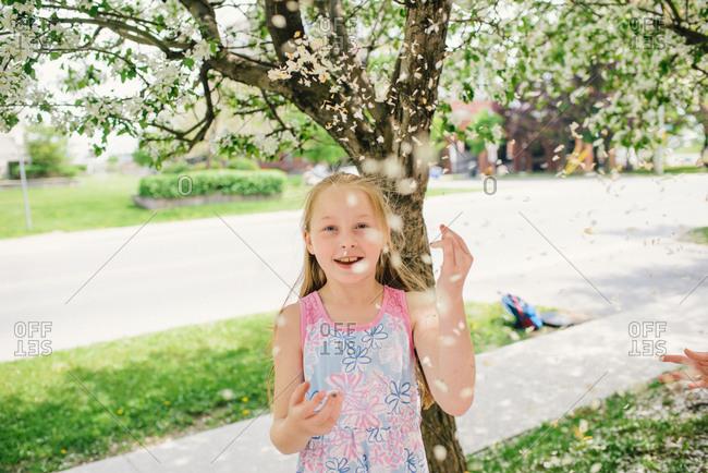 Girl throwing blossom on suburban street, portrait