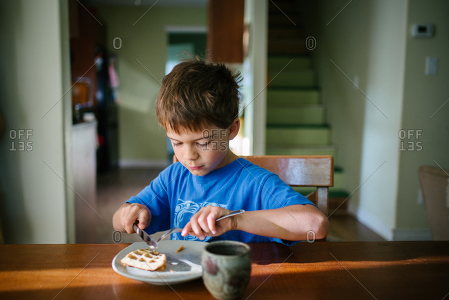Boy eating waffle breakfast at kitchen table