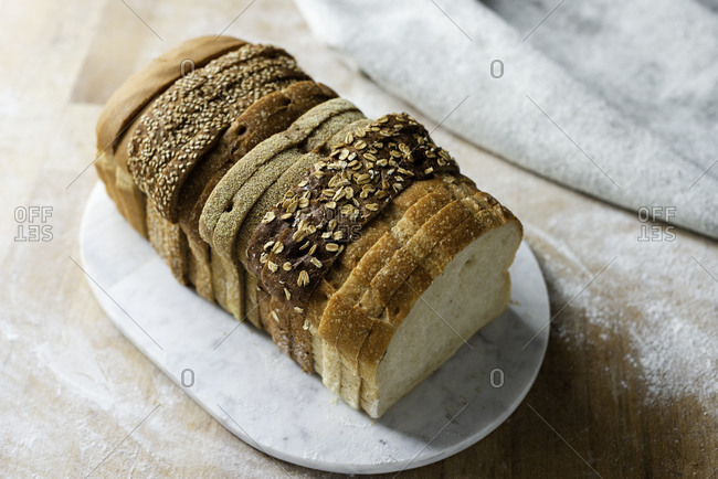 Sliced loaf made up of variety of white and wholemeal slices on cutting board, high angle view