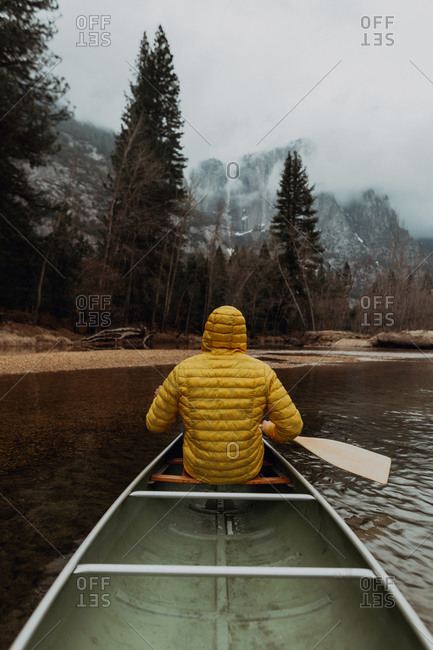 Young male canoeist rowing canoe on river, rear view, Yosemite Village, California, USA