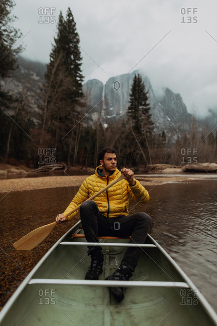 Young male canoeist rowing canoe on river, Yosemite Village, California, USA