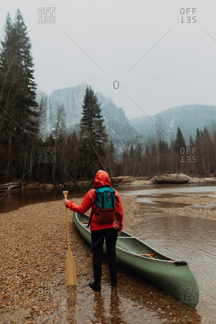 Young female canoeist preparing canoe in river, rear view, Yosemite Village, California, USA