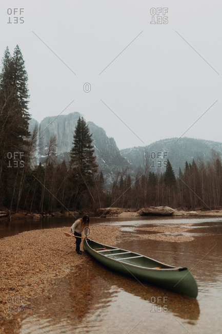 Young female canoeist pulling canoe from river, Yosemite Village, California, USA