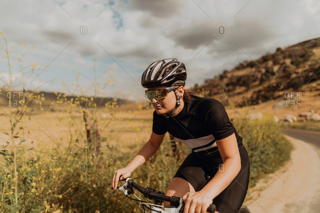 Young female cyclist cycling on rural road, Exeter, California, USA