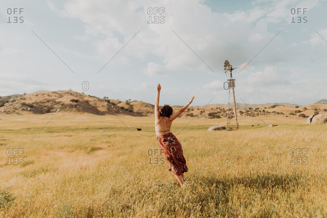 Young woman dancing in field landscape, rear view, Exeter, California, USA