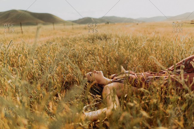 Young woman lying in field of long grass, Exeter, California, USA