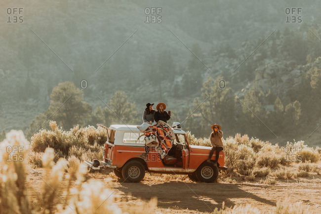 Friends sitting on rooftop of off road vehicle, Kennedy Meadows, California, US