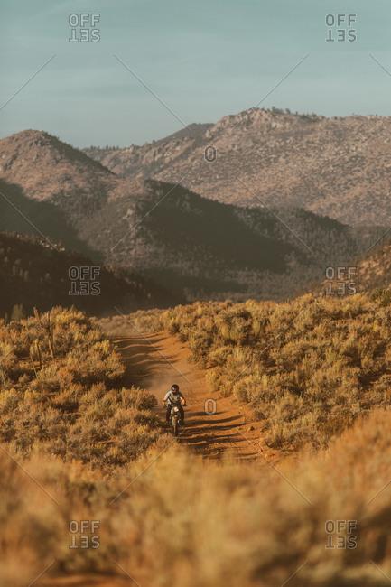 Motorbiker riding through landscape of Kennedy Meadows, California, US