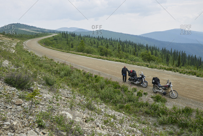 Senior male motorcyclist on rural mountain roadside with motorbike, high angle portrait, Dawson Creek, Canada