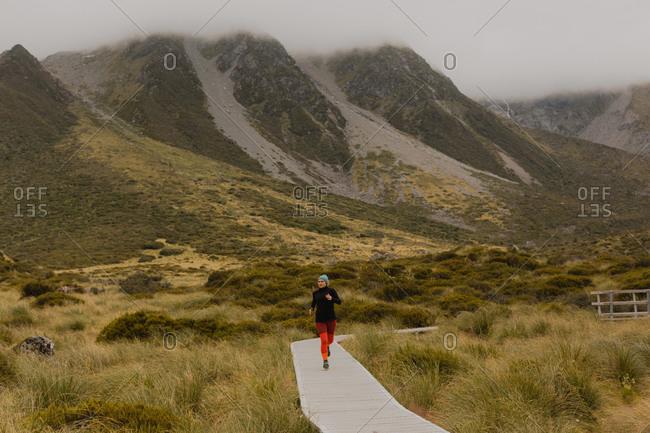 Woman jogging on trail path, Wanaka, Taranaki, New Zealand