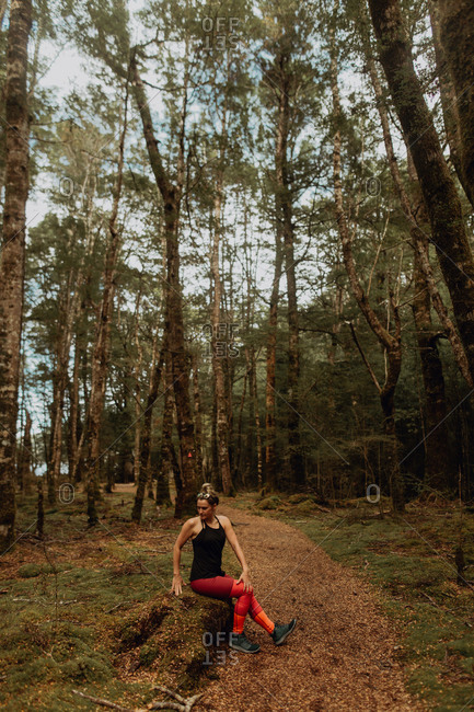 Woman stretching in forest, Queenstown, Canterbury, New Zealand