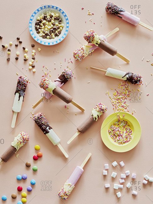 Chocolate top ice lollies and sprinkles on table