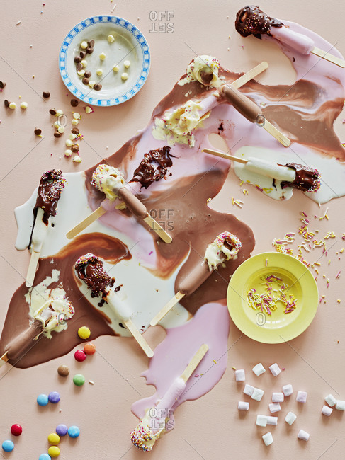 Chocolate top ice lollies melting and sprinkles on table