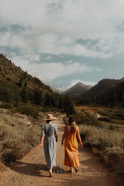 Two woman in maxi dresses strolling on rural valley road, rear view, Mineral King, California, USA