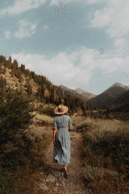 Young woman in stetson and maxi dress strolling on rural valley dirt track, rear view, Mineral King, California, USA