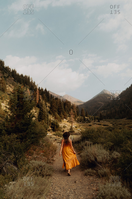 Woman in orange maxi dress strolling on rural valley dirt track, rear view, Mineral King, California, USA
