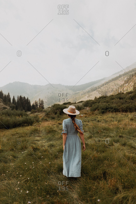Young woman in stetson and maxi dress strolling in rural valley, rear view, Mineral King, California, USA
