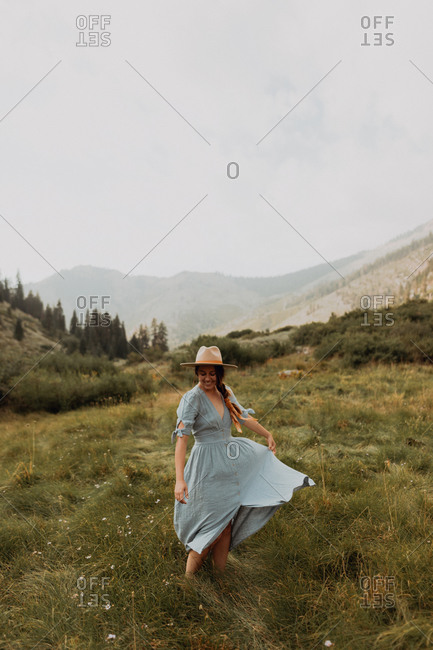 Young woman in stetson swirling maxi dress in rural valley, Mineral King, California, USA