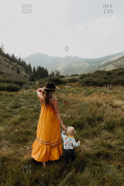 Mother holding toddler daughter's hand in rural valley, rear view, Mineral King, California, USA