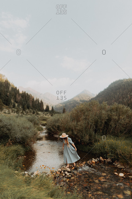 Young woman in stetson crossing stepping stones in rural river, Mineral King, California, USA