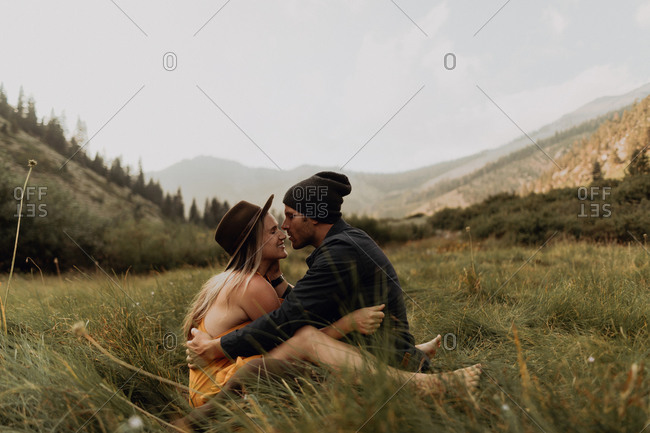 Mid adult couple sitting down hugging in rural valley, Mineral King, California, USA