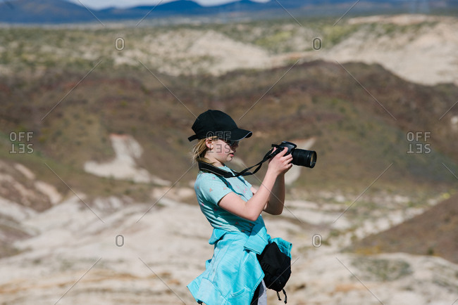 Girl taking photograph of view, Red Rock Canyon, Cantil, California, United States