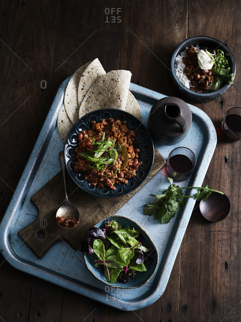 Rustic low key still life with tray of chilli con carne, salad and coffee, overhead view
