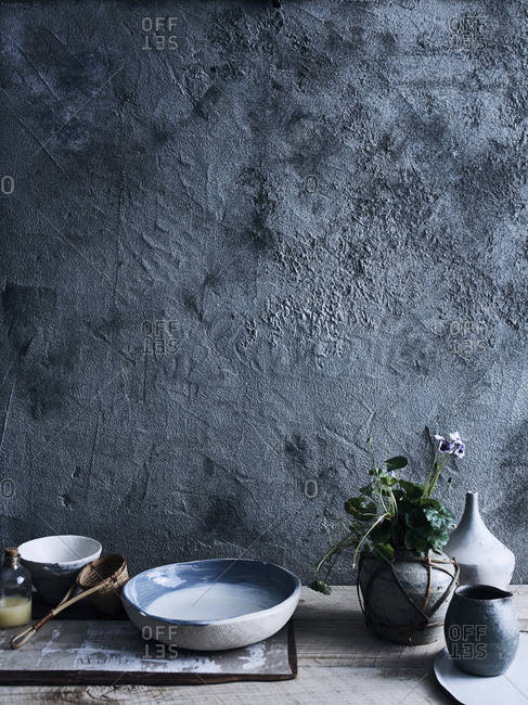 Ceramic bowls and vases against background of unfinished wall