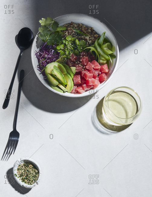High key still life with tuna and quinoa poke bowl on white table, overhead view