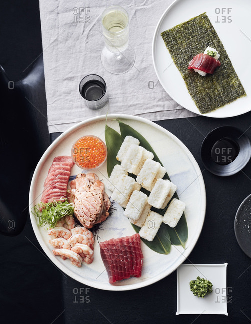 Plate of sashimi and sushi served with white wine