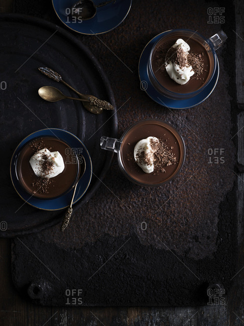Rustic low key still life with coffee, chocolate truffle cups on table, overhead view