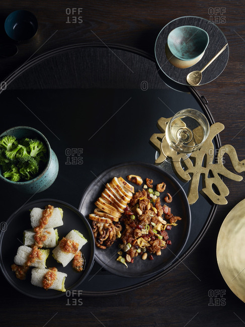 Rustic low key still life with dish of fungus cabbage roll and grilled whole squid on table, overhead view