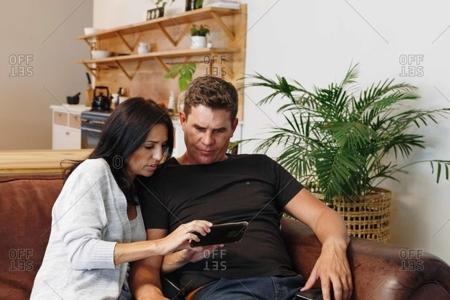 Couple reading text message on mobile phone at home