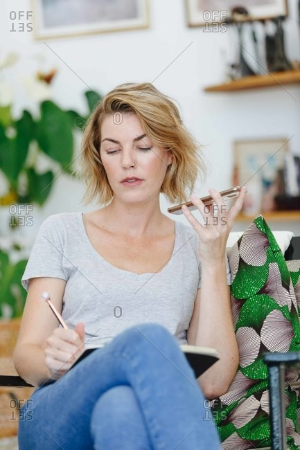 Businesswoman using cellular phone and writing notes in office