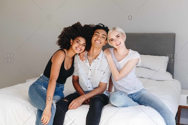 Happy young man and two female friends sitting on bed, portrait