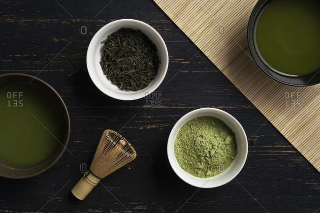Still life of matcha tea preparation with whisk and bowls of matcha tea and tea powder, overhead view