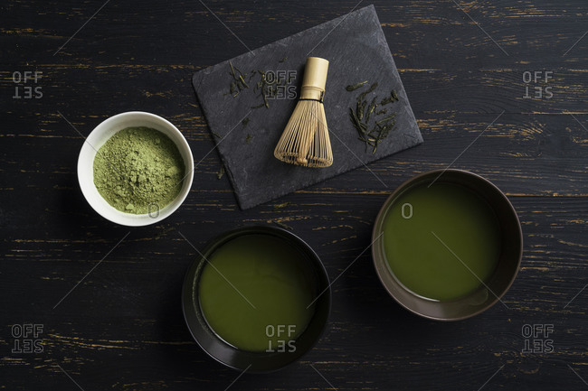 Still life of matcha tea preparation with whisk and bowls of matcha tea and tea powder, overhead view, low key