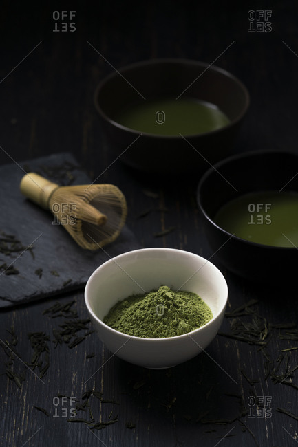 Still life of matcha tea preparation with whisk and bowls of matcha tea and tea powder, low key