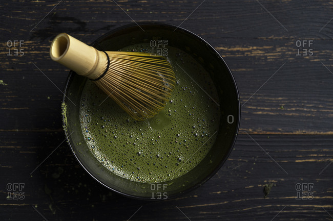 Still life of matcha tea preparation with whisk in bowl of matcha tea, overhead view, low key