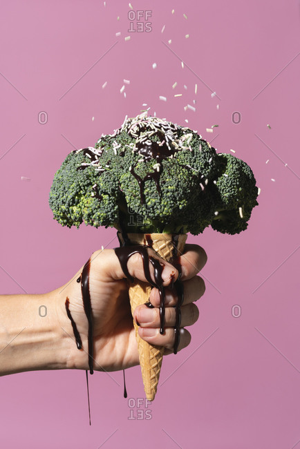Studio shot of man's hand holding ice cream cone with broccoli on top, dripping chocolate sauce and sprinkles, against pink background