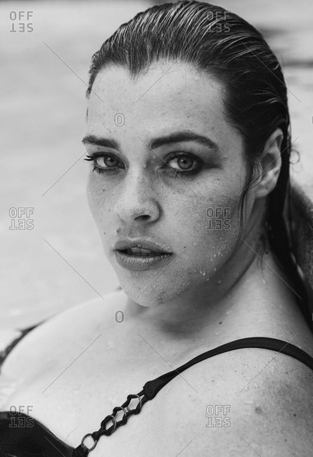 Sultry mid adult woman with wet hair leaning against outdoor swimming poolside, black and white head and shoulder portrait, Cape Town, South Africa
