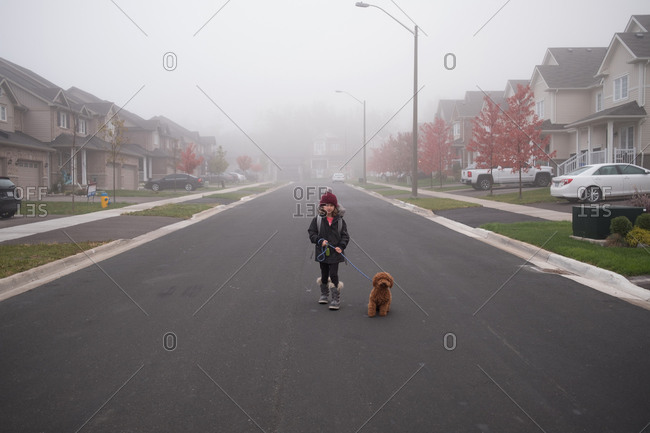 Girl walking dog in middle of misty suburban road, full length portrait