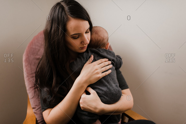 Young woman holding baby son in living room armchair