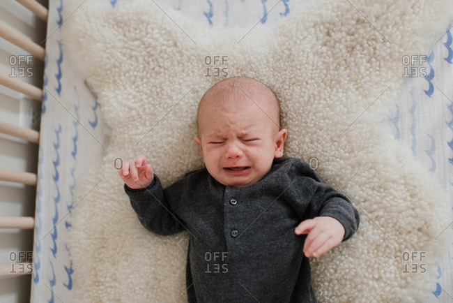 Baby boy crying while lying on sheepskin rug in crib, overhead view