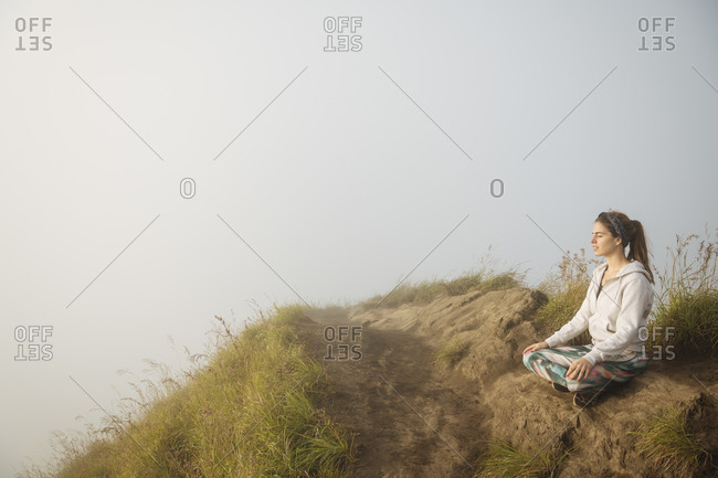 Young woman practicing yoga on top of misty mountain, Bali, Indonesia