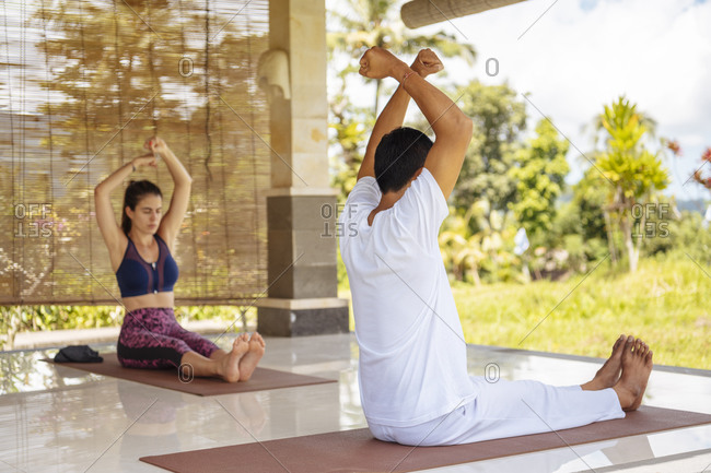 Young female tourist practicing yoga with teacher, Bali, Indonesia