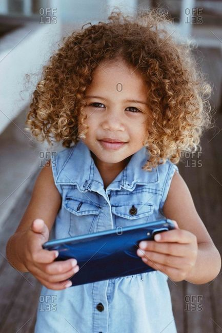 Little girl using smartphone on porch