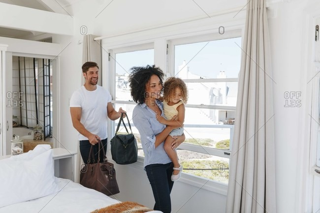 Couple and daughter leaving bedroom in beach house