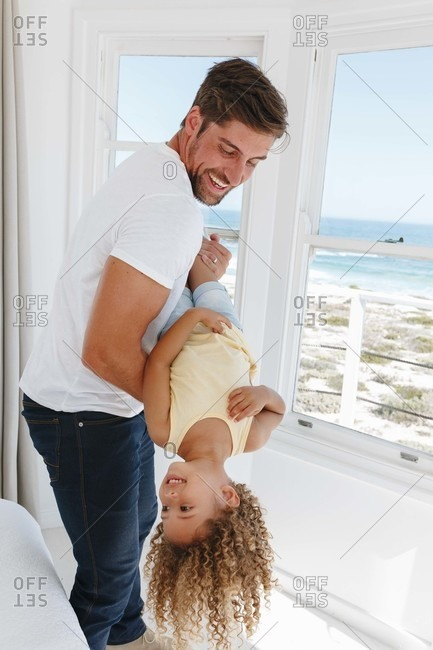 Father holding daughter upside down in beach house